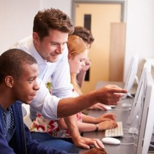 Image of teacher showing student how to do something on a computer