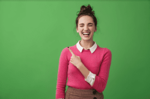 student in front of a green screen